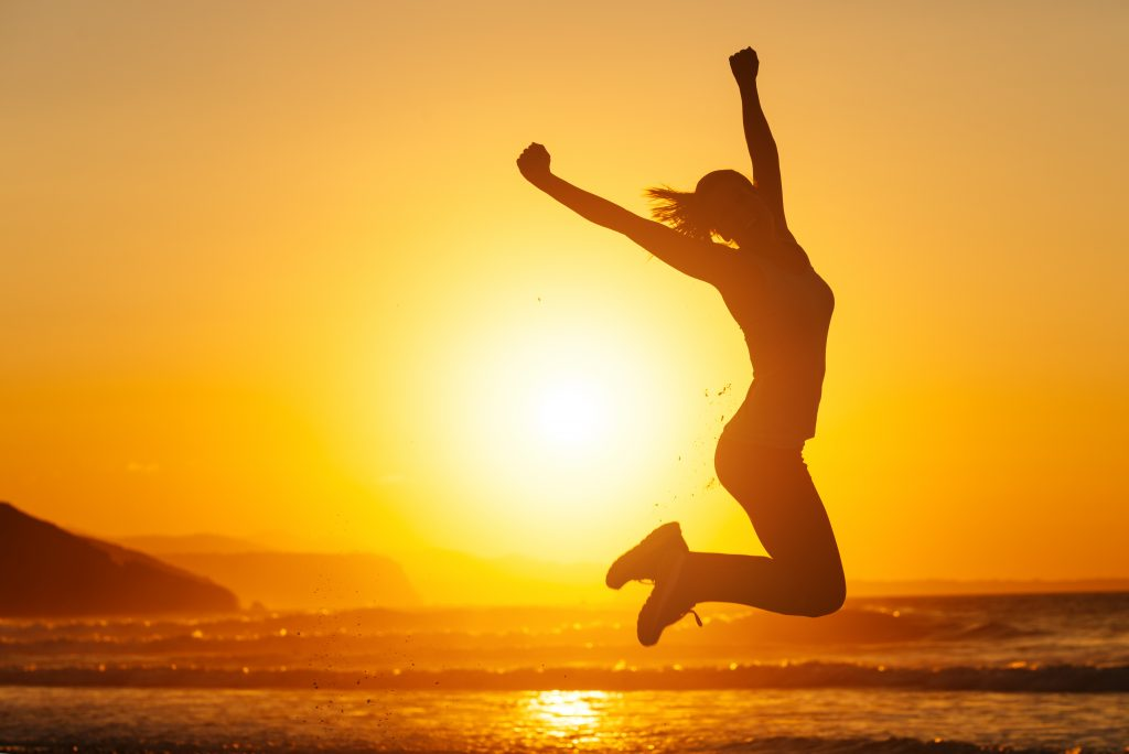 Woman jumping in front of sun